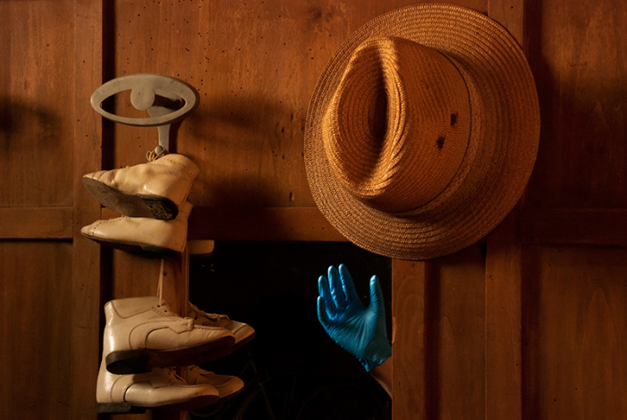 Hand with blue glove reaching for the hat